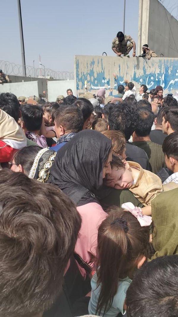 महिलाएं अपने बच्चों को लिए घंटों धूप में इंतजार करते थक जा रही हैं, लेकिन उन्हें हवाई अड्डे के अंदर जाने नहीं दिया जा रहा।