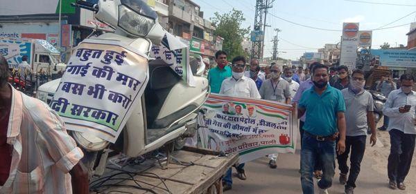मोटूभाई के नेतृत्व में रैली के रूप में धरना स्थल पर जाते कांग्रेसी। साथ में विरोध स्वरूप स्कूटी को ठेले पर रखकर ले जाते हुए।