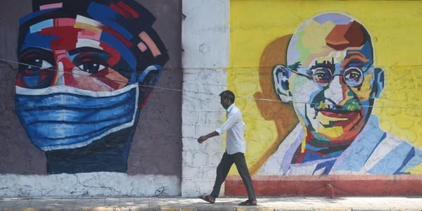 मुंबई में मास्क के लिए जागरूक करने वाली एक वाल पेंटिंग के सामने से गुजरता युवक।