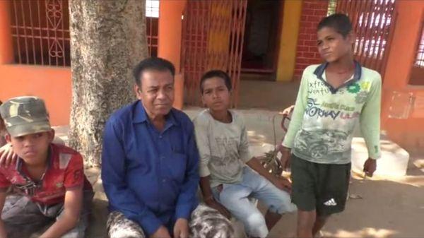 गोंडपेंड्री गांव के बुजुर्ग और बच्चोंें एक चबूतरे पर साथ बैठे हुए, गांव में होली का उत्साह नहीं हैं।