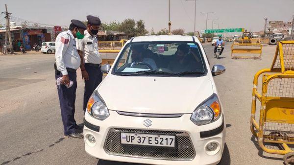 बीकानेर में जैसलमेर रोड पर वाहनों को रोककर पूछता करते यातायात कर्मी।