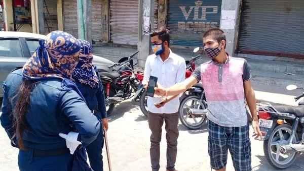 बाडमेर में पुलिस दो युवकों से बाहर पूछने का कारण बताते हुए।