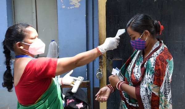 कोलकाता में मतदान करने आई महिला वोटर की थर्मल स्कैनिंग करती महिला मतदान कर्मचारी।