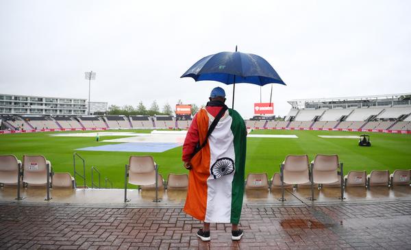 बारिश रुकने का इंतजार करता भारतीय फैन।