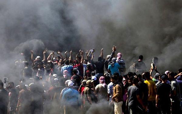 गाजा पट्टी के पास बॉर्डर क्षेत्र में इजराइल की पुलिस के सामने प्रदर्शन करते फिलिस्तीनी।