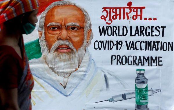 मुंबई में वैक्सीनेशन के लिए जागरूक करने वाली दीवार के बगल से गुजरती एक महिला।