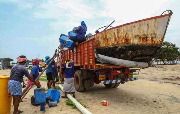 केरल के कोझीकोड में अलर्ट के बाद ट्रक पर नाव लादकर ले जाते मछुआरे।