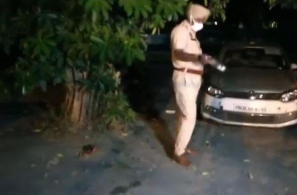 JE की फेंकी शराब की बोतल जब्त करता पुलिस कर्मी।