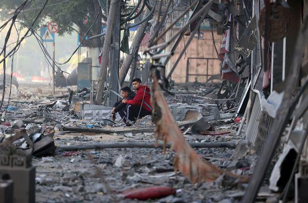बम विस्फोट में नष्ट हुए एक घर के बाहर बैठे दो फिलिस्तीनी बच्चों ने अब तक दोनों पक्षों के हमलों में 27 बच्चों को मार डाला है।