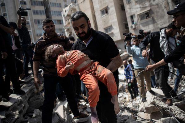गाजा पट्टी पर एयरस्ट्राइक के बाद मलबे में दबे बच्चे का शव लेकर जाता फिलिस्तीनी।