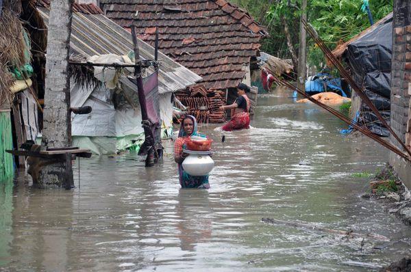 दक्षिण 24 परगना जिले के नमखाना ग्राम पंचायत में घरों में पानी घुसने के बाद जरूरी सामान लेकर सुरक्षित स्थान पर जाती महिला।