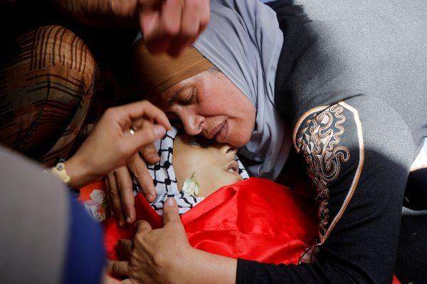 इजराइल की एयरस्ट्राइक में अपने बच्चे की मौत का दुख मनाती फिलिस्तीनी महिला।