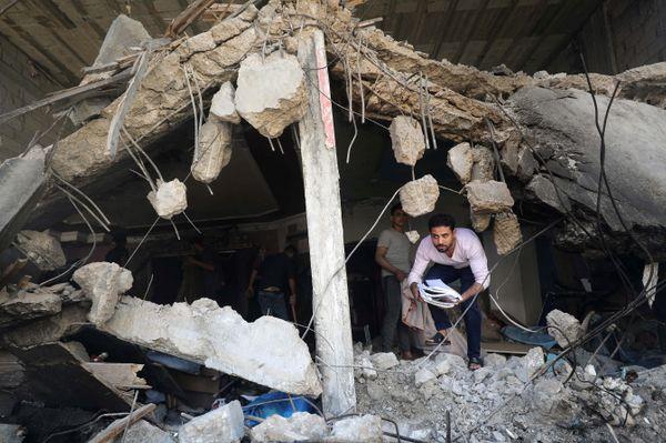 इजराइल की एयरस्ट्राइक में तबाह हुए अपने घर से जरूरी सामान निकालते फिलिस्तीनी।