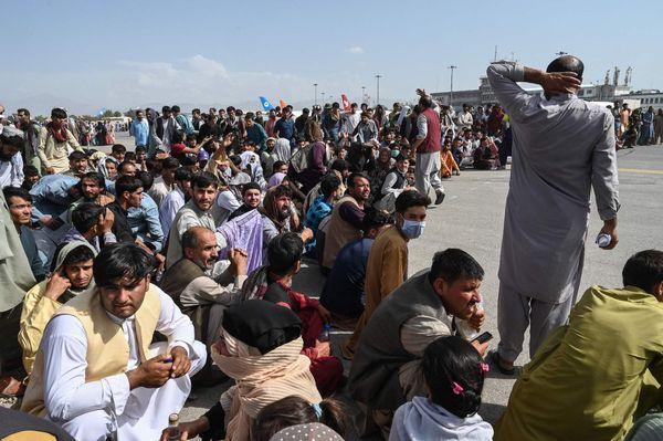 काबुल एयरपोर्ट के अंदर विमान का इंतजार करते अफगानी नागरिक।