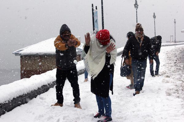 श्रीनगर में बर्फबारी का मजा लेते टूरिस्ट।