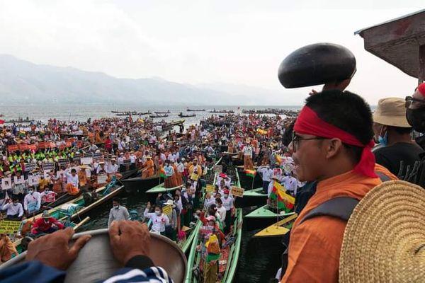 म्यांमार के प्रसिद्ध इनले लेक में लोगों ने नावों में नदी के बीच प्रदर्शन किया।