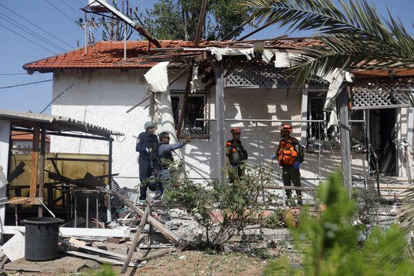 गाजा पट्टी से इजराइल पर दागे गए रॉकेट से तबाह घर का मुआयना करती इजराइली पुलिस।