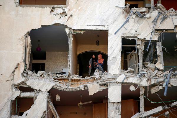 गाजा पट्टी पर इजराइली एयरस्ट्राइक में टूटे घर को दिखाती फिलिस्तीनी महिलाएं।