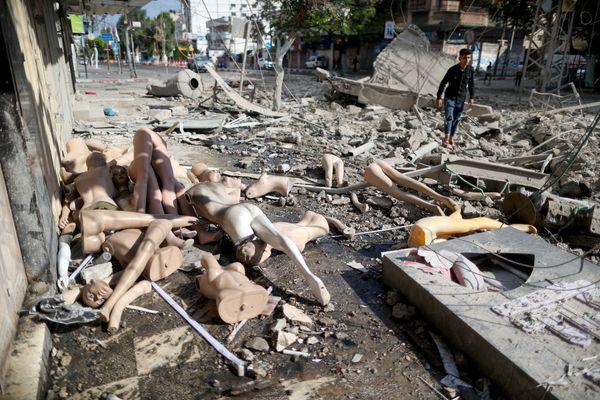 इजराइल की एयरस्ट्राइक में गाजा पट्टी पर ढहीं दो बिल्डिंग। यहां कपड़ों की एक दुकान थी, जिसके पुतले सड़क पर बिखर गए।