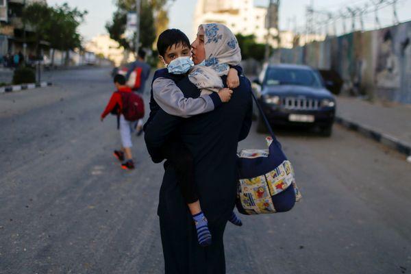 अपने बच्चे को लेकर हमले से बचने के लिए सुरक्षित स्थान पर जाती फिलिस्तीनी महिला।