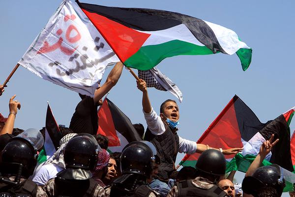 प्रदर्शनकारियों के हाथ में जॉर्डन और फिलिस्तीन दोनों का ही झंडा था।