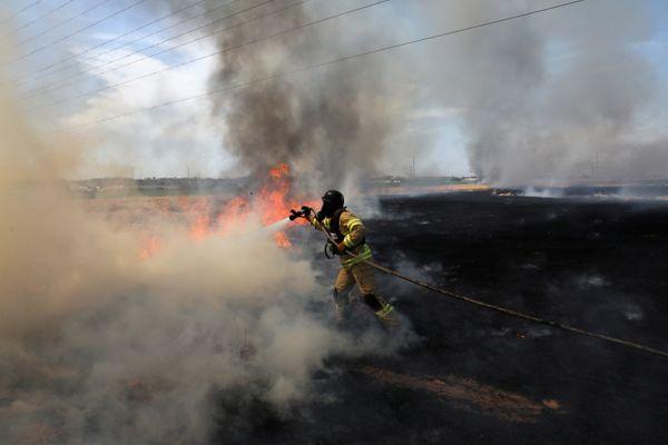 दंगाइयों की लगाई आग को बुझाता इजराइल का एक फायर फाइटर।