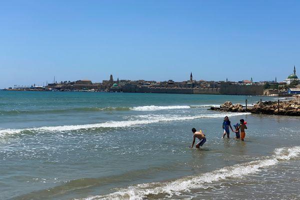 इज़राइल में युद्ध की स्थिति।  इस बीच इज़राइल के बच्चे भूमध्य सागर के तट पर मस्ती करते हैं, यह अरब और इज़राइल के बीच समुद्री सीमा है।