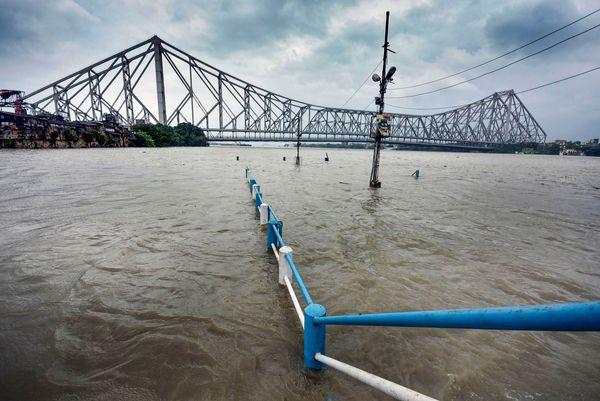 फोटो कोलकाता के हावड़ा ब्रिज की है। तूफान के साथ हुई बारिश के कारण नदी पर बने इस ब्रिज के पास रेलिंग तक पानी भर गया।