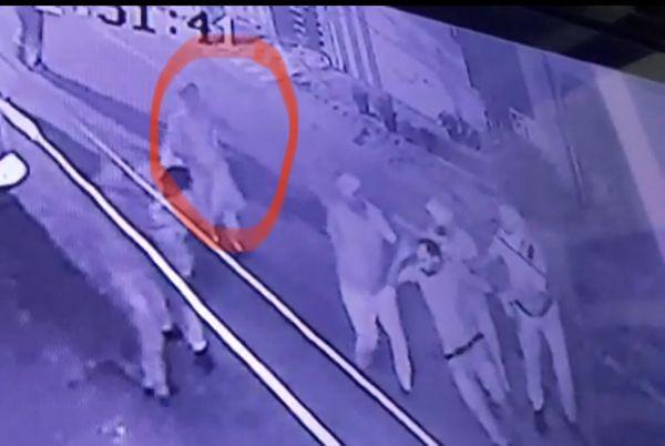CCTV फुटेज में हमलावर को पकड़कर ले जाती पुलिस के पीछे आती महिला।