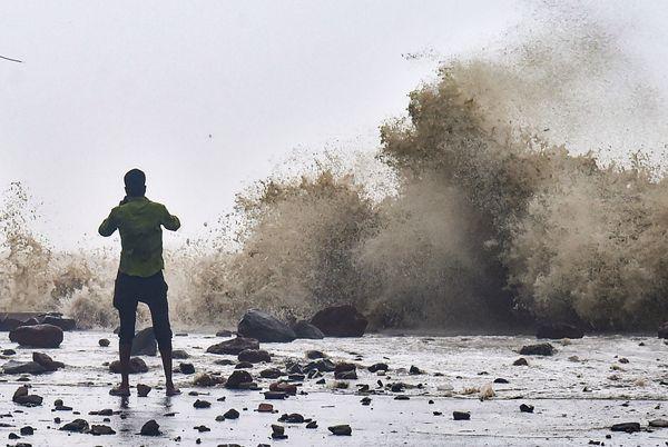 तट के किनारे खड़े होकर यास तूफान से समुंदर में उठ रही लहरों की फोटो खींचता युवक।