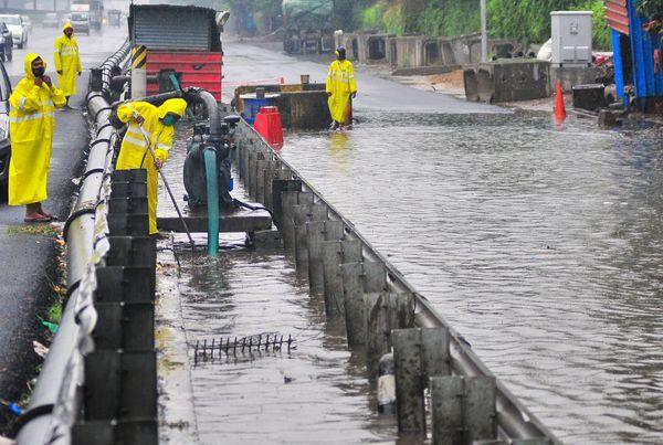 गुरुग्राम की सड़कों पर पानी भरने के बाद उसे निकालते नेशनल हाइवे अथॉरिटी के वर्कर।