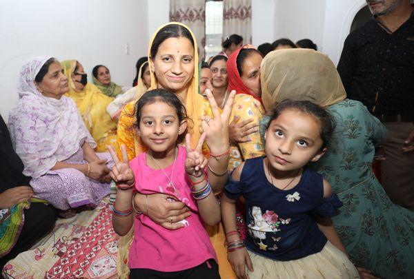 मीनू की गोद में बैठी उनकी बेटी को अब पापा के घर आने का इंतजार है। फोटो- अंकुर सेठी