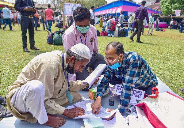 असम के नगांव में मतदान से एक दिन पहले चुनावी सामग्री की जांच करते पोलिंग अधिकारी।