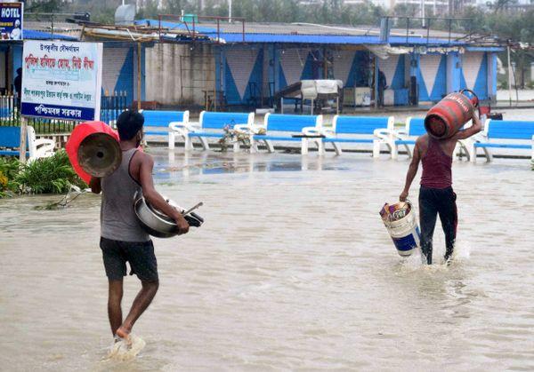 बारिश का पानी जब घरों में घुस गया तो इन्होंने सबसे पहले भोजन की व्यवस्था करना जरूरी समझा। फोटो पूर्वी मेदिनीपुर की है।