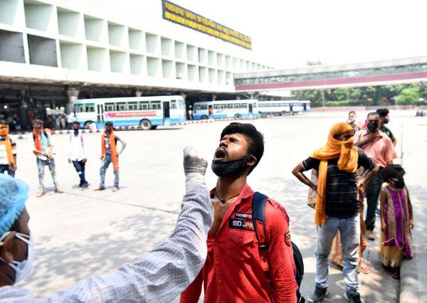 नई दिल्ली में बढ़ते कोरोना मामलों के बीच कश्मीरी गेट पर स्वास्थ्यकर्मी एक यात्री से सैम्पल कलेक्ट करते हुए।