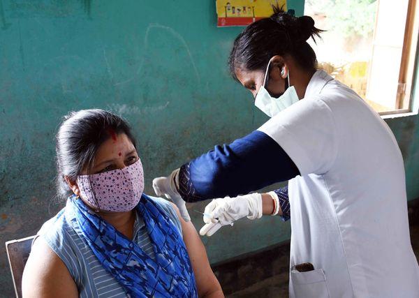 असम के नगांव में महिला को कोरोना वैक्सीन का पहला डोज लगाती हेल्थकेयर वर्कर।