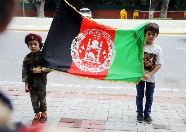 दो बच्चे अफगानिस्तान का झंडा थामे हुए नजर आए। इनमें से एक बच्चा अफगानी सैनिकों जैसी वर्दी पहने हुए था।