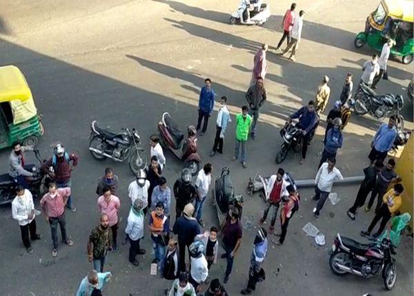 कार की टक्कर से बिजली का पोल गिरने के बाद मौके पर जमा भीड़।