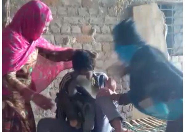 युवक के गले में जूतों की माला पहनाकर मारपीट करती महिलाएं।
