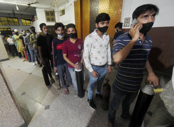नई दिल्ली में फ्री ऑक्सीजन रिफिल के लिए सिलेंडर लेकर वॉल्ड सिटी पहुंचे मरीज के रिश्तेदार।