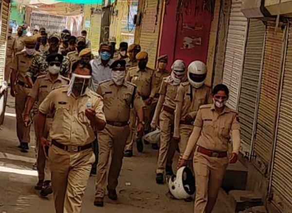 पुलिस अधिकारियों की अगुवाई में फ्लैग मार्च निकालते पुलिस जवान।