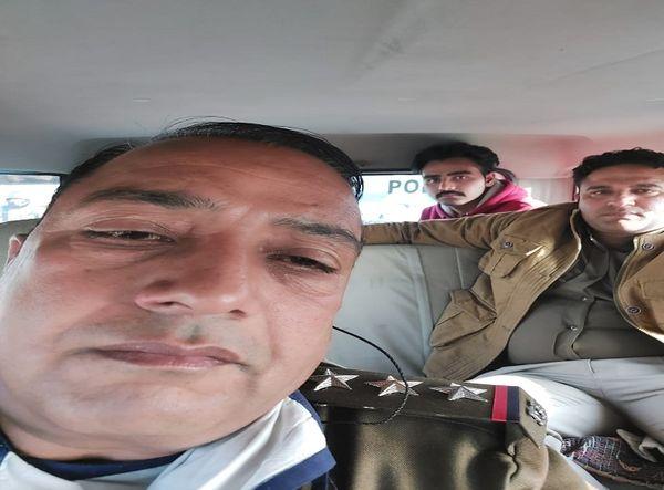 पुलिस की गाड़ी में पीछे बैठा अपहरण व लूट का पीड़ित किसान आकाश।
