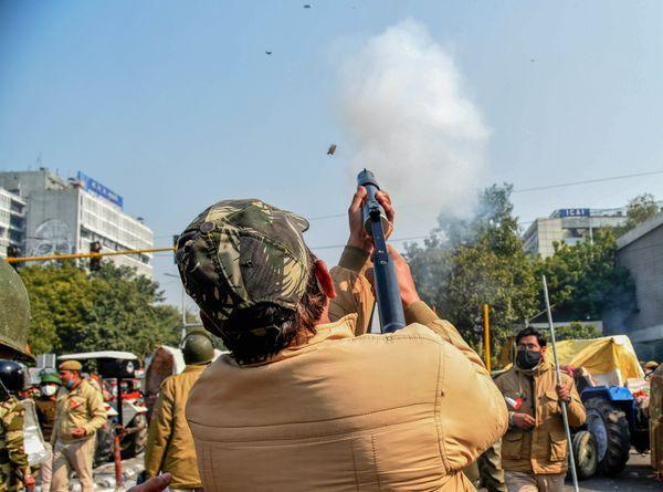 आईटीओ में प्रदर्शनकारी भीड़ पर आंसू गैस के गोले छोड़ते पुलिस के जवान।