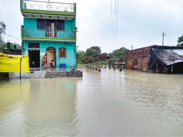 बाढ़ के पानी में घिरे घर। लोग दूसरी मंजिल पर रहने को मजबूर।