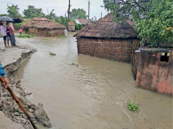 बांध का होता कटाव और घरों में घुसा पानी।