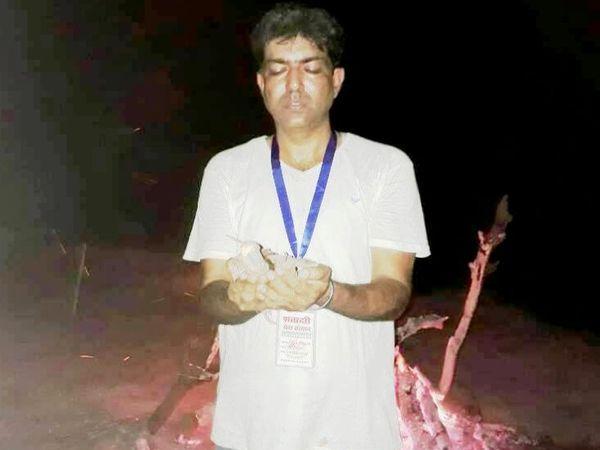 लावारिस शव का अंतिम संस्कार करते नवीन। - Dainik Bhaskar