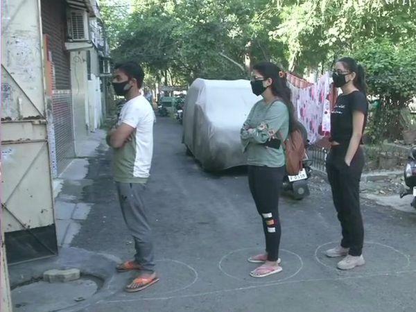 दिल्ली में कुछ स्थानों पर लोग किराना की दुकानों पर सोशल डिस्टेंसिंग का पालन कर रहे हैं।