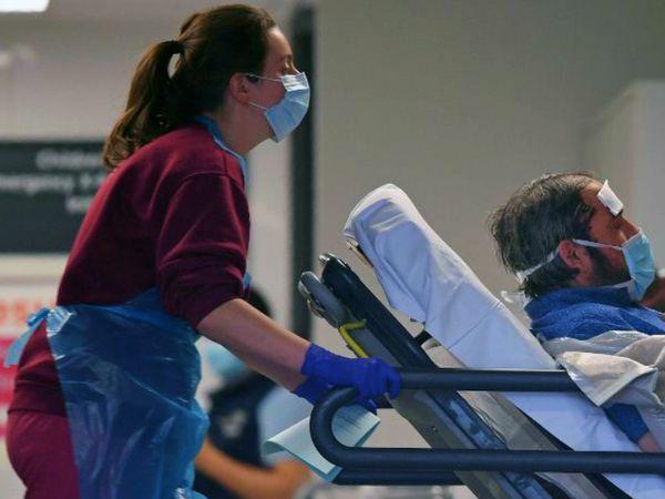 लंदन के सेंट थॉमस अस्पताल में कोरोना मरीज को ले जाती नर्स। ब्रिटेन में मंगलवार से बुधवार शाम 6 बजे तक 563 लोगों की संक्रमण से मौत हो गई। - Dainik Bhaskar