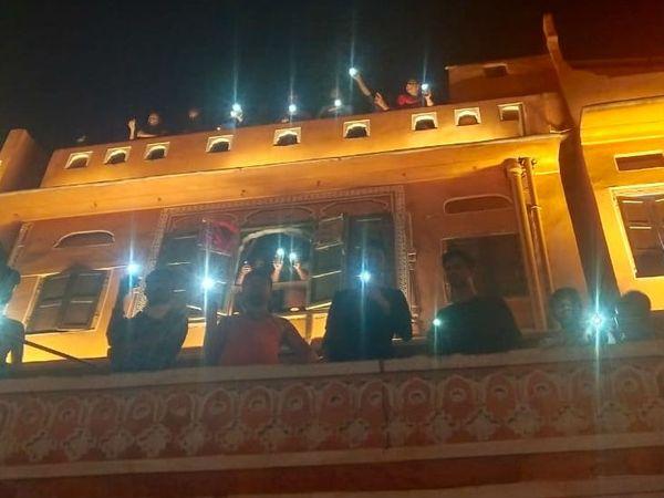 जयपुर में घर की छत और बालकनी से टॉर्च जलाते युवा।
