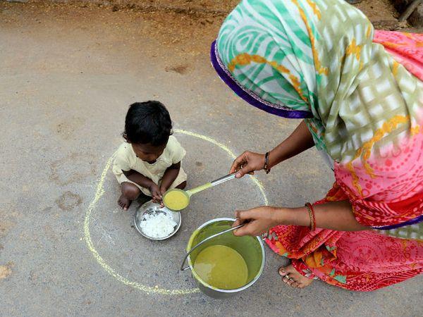 लॉकडाउन के बीच बेघर और गरीब समाजसेवियों की ओर से उपलब्ध कराए जा रहे खाने पर निर्भर हैं। प्रयागराज में ऐसे ही एक बच्चे को खाना परोसती महिला।